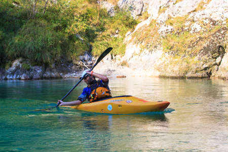 KOBARID, SLOVENIA - AUGUST 19: An sport kayaker rowing in the Soca river, August 19, 2012 in Kobarid, Slovenia