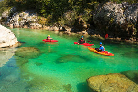 KOBARID, SLOVENIA - AUGUST 20: Sport kayakers rowing in the Soca river, August 20, 2012 in Kobarid, Slovenia