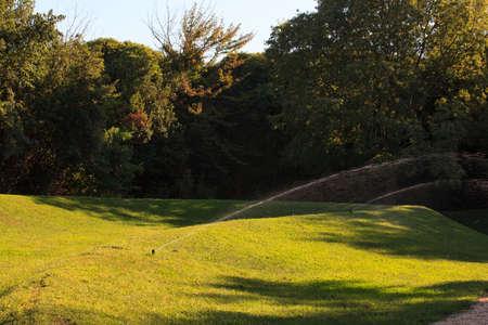 lawn sprinkler: Lawn sprinkler spraying water over green grass