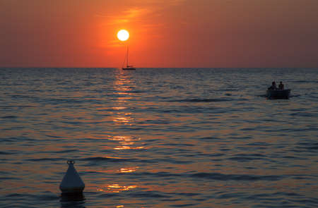 Sunset at sea with a sailboat in Trieste photo