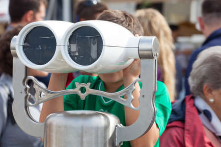 Child looking inside a tourist binoculars next to the sea in Trieste photo