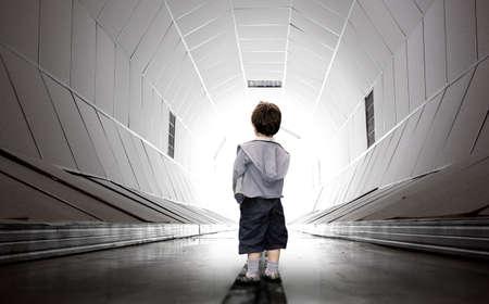 sconosciuto: Bambino spaventato a camminare verso il tunnel bianco Archivio Fotografico