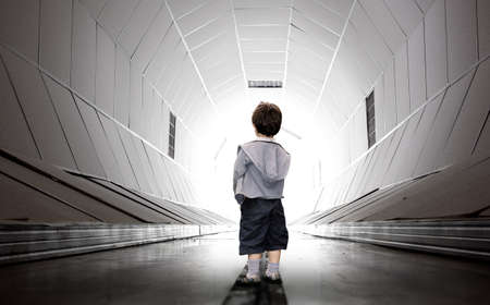 near death: Frightened child walking towards the white tunnel Stock Photo