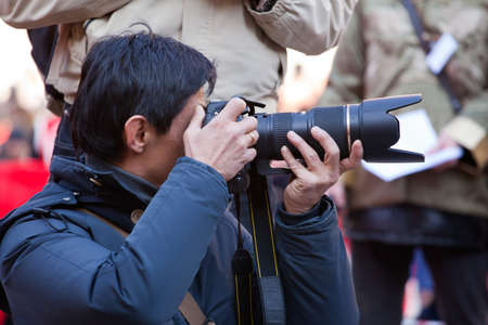 Photographer taking a photo with DSLR camera Stock Photo - 18099604