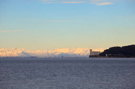 Julian Alps covered by snow behind the Miramare castle in\ Trieste