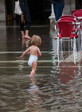 Child and mother in San Marco square in Venice during High water  photo