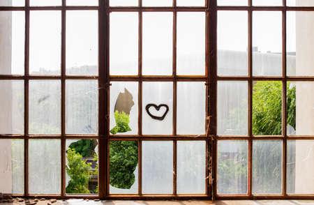 pared rota: Coraz�n pintado en las ventanas rotas del edificio abandonado Foto de archivo