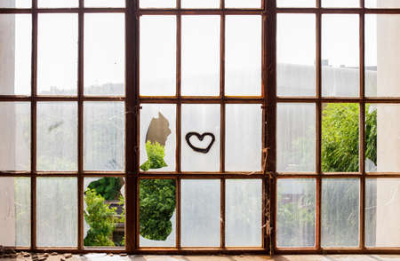 Heart painted on broken windows of abandoned  building photo