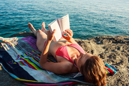 Girl Reading book in the beach, Pantelleria Stock Photo - 22485780