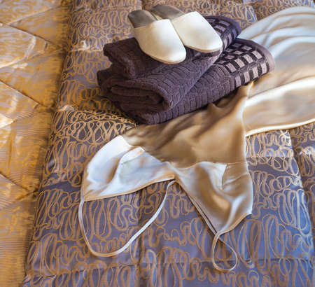 White female slippers on the towels in the bed photo