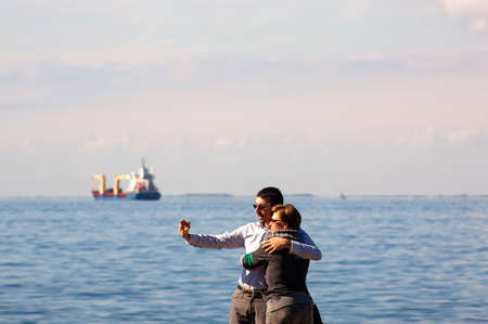 trieste: TRIESTE, ITALY - OCTOBER, 10: Couple of lovers take selfie next to the Trieste sea on October 10, 2013