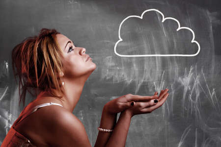 Cloud computing concept. Girl looking to the cloud drawing on blackboard photo
