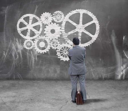 Finance concept. Businessman looking gears on chalkboard photo