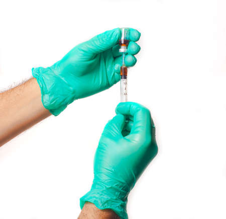 intramuscular: Hands of the doctors with green glowes filling a syringe