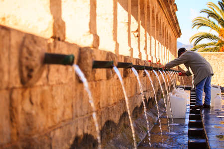 austere: LEONFORTE, ITALY - JANUARY, 08: Man filling cans with fountain water on January 08, 2015
