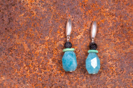 chalcedony: Close up of chalcedony earrings on rusty iron, manufactured by Ornella Salamone Stock Photo