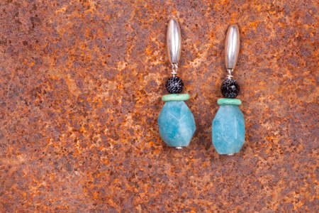 manufactured: Close up of chalcedony earrings on rusty iron, manufactured by Ornella Salamone Stock Photo