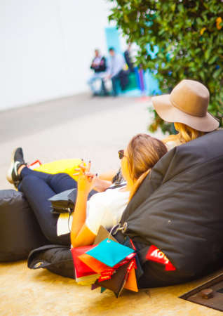 pouf: MILAN ITALY APRIL 16: Two young girls lie down on pouf space location at Tortona during Milan Design Week on April 16 2015