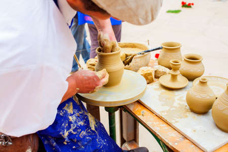 ceramicist: MILAN, ITALY - MAY, 20: Pottery maker uses a kick wheel to hand mold a pot from clay during the Expo, universal exposition on the theme Feeding the planet, Energy for life on May 20, 2015 in Milan Editorial