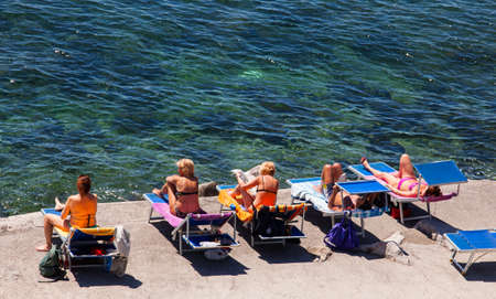 wetting: TRIESTE, ITALY - MAY, 10: People tanning in the Trieste seaboard on May 10, 2015