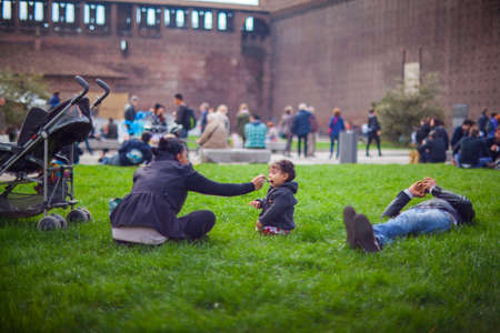 pic nic: MILAN, ITALY - MARCH, 29: Mother in the park feeding her baby girl with a spoon on March 29, 2015 Editorial