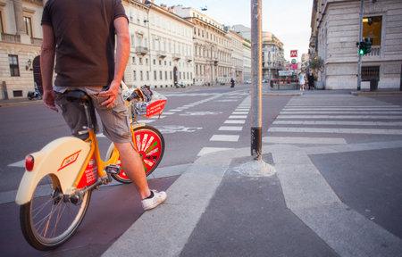 rented: MILAN, ITALY - JUN, 21:Man on rented bike along the Milan street on Jun 21, 2015 Editorial