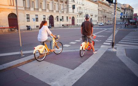 rented: MILAN, ITALY - JUN, 21: Couple on rented bikes along the Milan street on Jun 21, 2015