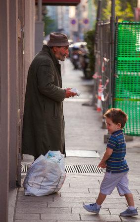 oap: MILAN, ITALY - JUN, 21: Beggar and child in the street on Jun 21, 2015