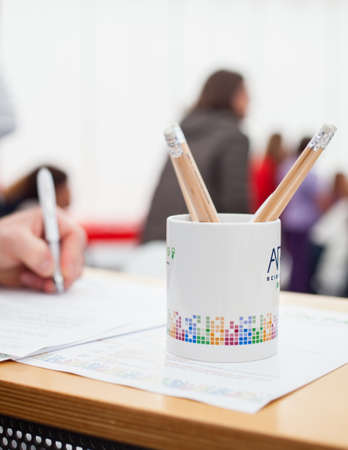 filling out: Close up of pencil box, in the background caucasian hand fill a form Stock Photo
