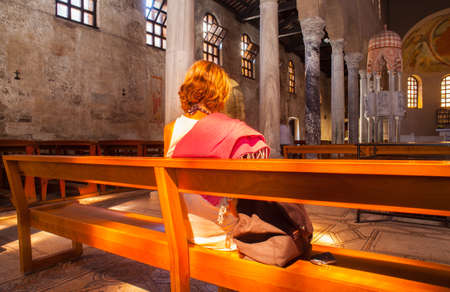 cleric: GRADO, ITALY - AUGUST, 29: Churchgoer praying in the Basilica of SantEufemiaon August 29, 2015