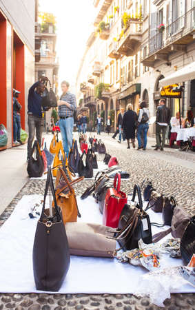 peddle: MILAN, ITALY - OCTOBER, 11: Counterfeit italian bags for sales in the street on October 11, 2015