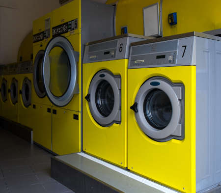 launder: Yellow industrial washing machines in a public laundromat