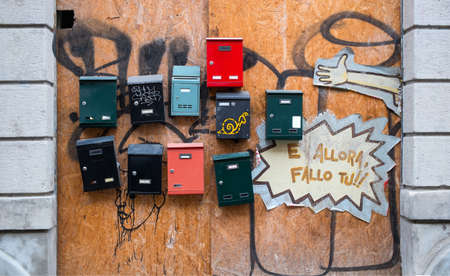 Italian post boxes on wooden wall - English translate of the italian phrase o the wooden wal is: and then do it yourself Banco de Imagens