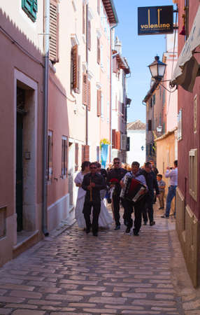 wedding guest: ROVINJ, CROATIA - APRIL 16: Bride and wedding guest walking in the Rovinjs street with musicians on April 16, 2016
