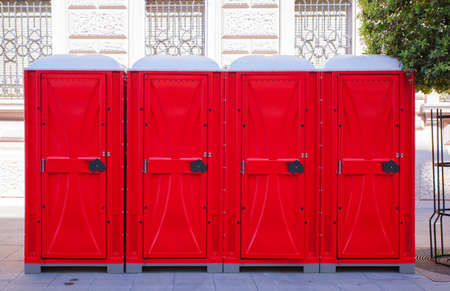 latrine: View of row of red portable toilets Stock Photo