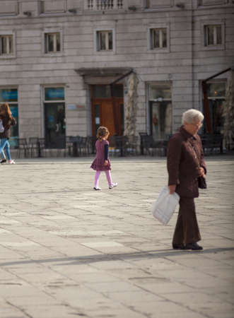 trieste: TRIESTE, ITALY - APRIL, 28: Child and old lady walking in the Trieste square on April 28, 2016 Editorial
