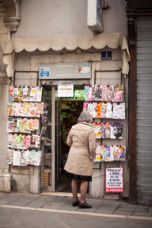 news stand: TRIESTE, ITALY - MAY, 01: Old lady looking magazines exposed in the news stand on May 01, 2016