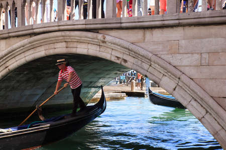 VENICE, ITALY - JUNE, 06: Venetian gondolier on typical gondola under the bridge in the Venice lagoon on June 06, 2016