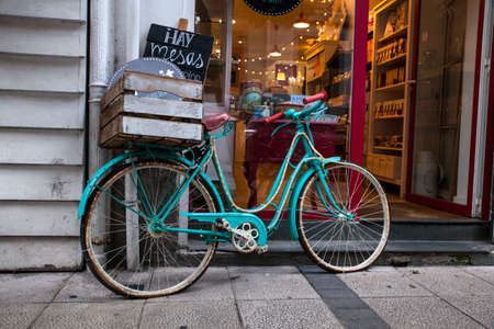 Green bicycle covered with many lights next to the shop Stock Photo