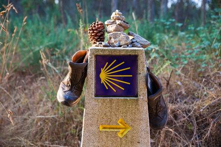 Stivaletti e pietra sul segnale di pietra, Simbolo della via di San Giacomo Archivio Fotografico - 69317360