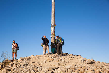 FONCEBADON, SPAIN - AUGUST, 05: Pilgrimns next to the iron cross called cruz de Hierro along the way of St. James on August 05, 2016
