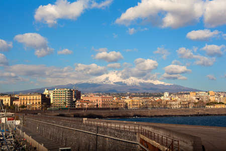 View of Catania from harbor, Etna volcano on background, Sicily. Italy