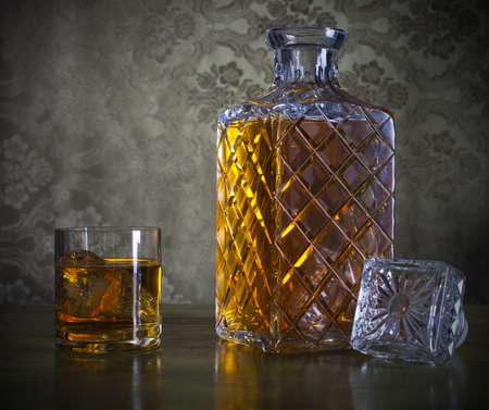 Whisky en una buena botella y vaso con hielo