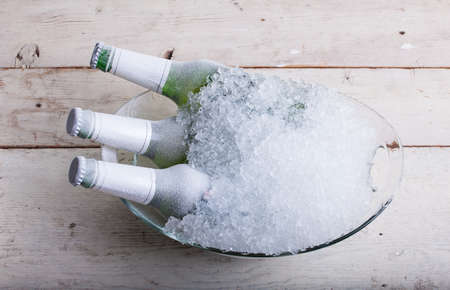 Three frozen glass bottles of beer immersed in the ice Фото со стока