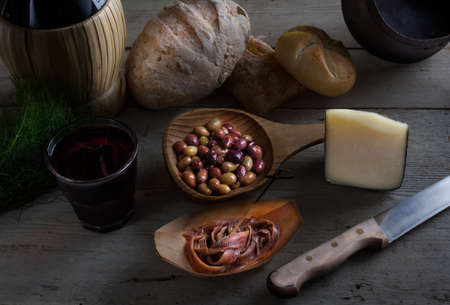 Italian slow food on the white table. Olives, cheese, bread, anchovies and red wine Stockfoto