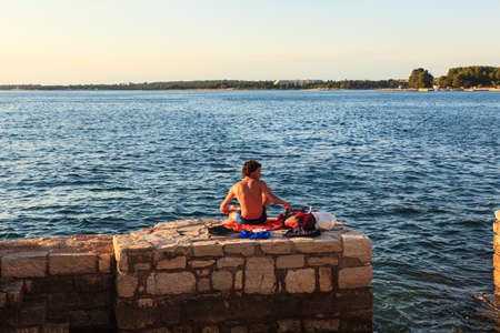 bather: POREC, CROATIA - JULY, 14: Man relaxing next to the sea on July 14, 2017