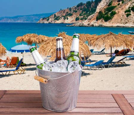Três, fechado, garrafas, de, cerveja, dentro, balde gelo, ligado, praia, fundo Foto de archivo