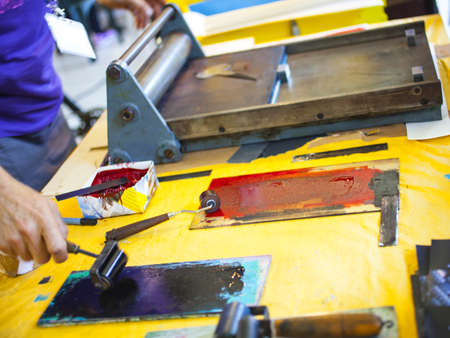 The artist working with vintage printing press