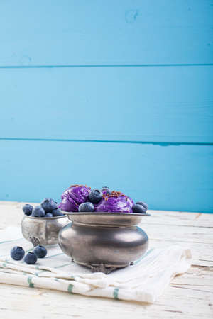 Fresh blueberry ice cream inside a pewter cup on old white wooden table