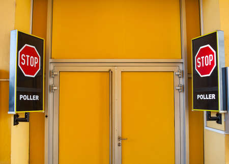 Stop signboards next to the closed yellow door Stock Photo